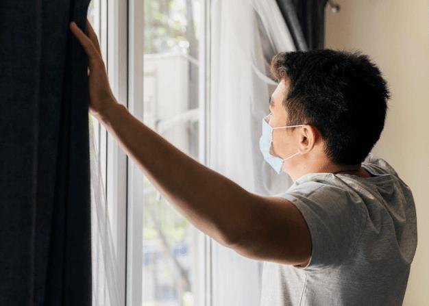 homem com mascara medica em casa durante a pandemia abrindo as cortinas da janela_23 2148781392